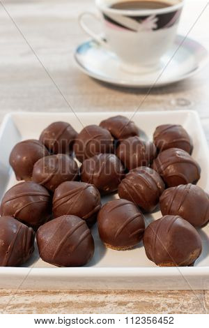 Close-up of chocolate balls and coffee on wooden table