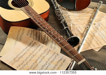 Acoustic guitar, soprano saxophone, violin, flute and note sheets on wooden background