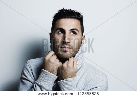 Atractive Young Man Warm Up With Pullover And Looking Sideways In Front Of Grey Background