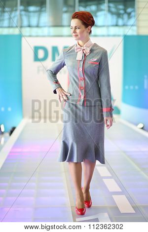 MOSCOW -JUL 09, 2015: A woman shows a gray uniforms flight attendant at a special screening of uniforms airlines DME RUNVAY in Domodedovo