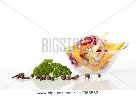 Salad with fresh onion and vegetables in glass plate, green parsley, peper, rosemary on white backgr