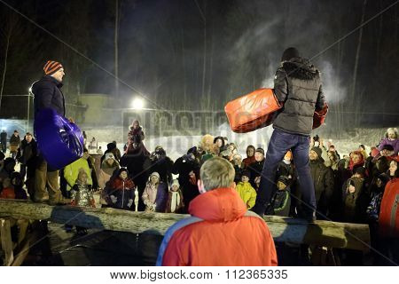 MOSCOW -?? FEB 22, 2015: Fighting on a log in the big boxing gloves on Shrovetide in the evening