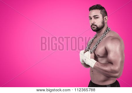Muscular man with a chain against pink background