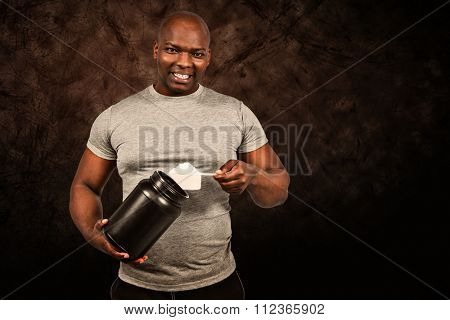 Fit man scooping protein powder against dark background