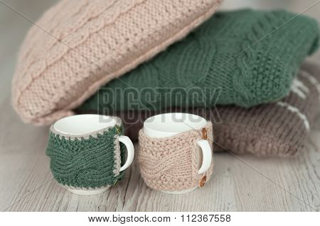 Three Knitted Pillows And Two Cups  On Wooden Board Background