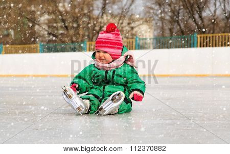 cute little girl sitting on ice with skates
