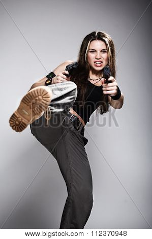Sexy woman holding gun on gray studio shot