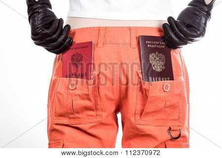 Front view of female hips in orange pants with russian passport and military ID in belt.