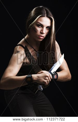 Sexy woman holding dagger. studio shot dark background