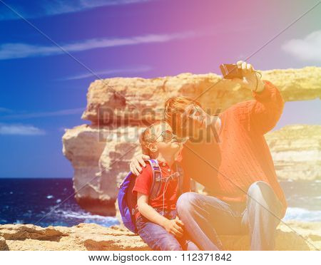 father and son making selfie photo against Azure Window on Gozo island