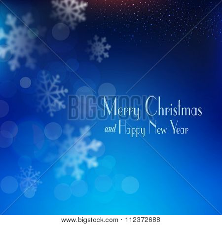 vector blue Christmas background with snowflakes blurred in the background