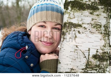 Pretty Young Woman Lean Against A Birch. Winter Time.