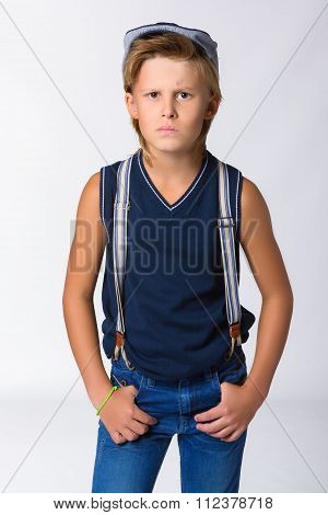 Cute blonde boy or teenager in half-length casual style blue jeans posing