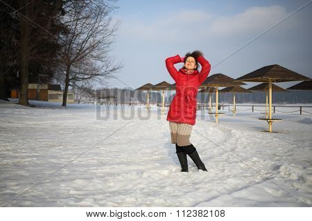 Woman in a red jacket holding up her hands hair standing on winter beach