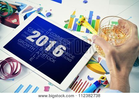 a young caucasian businessman celebrating the new year in his office observes a tablet computer with a tag cloud of goals for the 2016 for his company