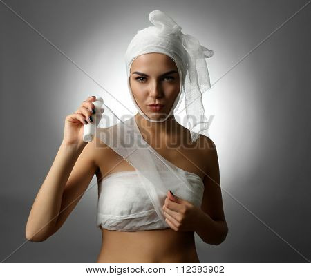 Young playful woman with a gauze bandage on her head and chest, on grey background