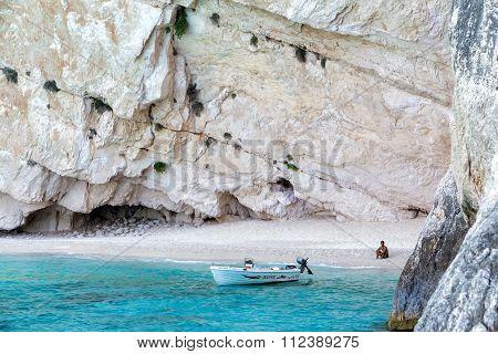 Tourist Sitting On The Beach Of Zakynthos Island, In Greece.