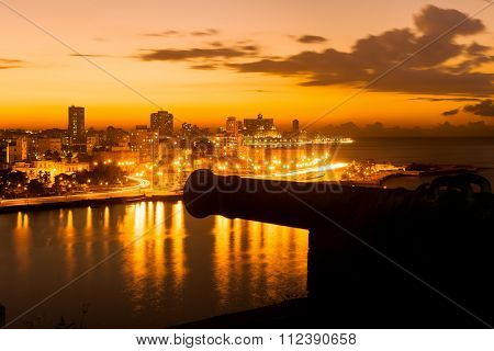 Sunset in Havana with a view of  the city skyline and an out of focus old spanish cannon on the foreground