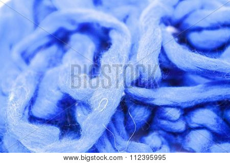 Navy blue piece of Australian sheep wool Merino breed close-up on a white background.