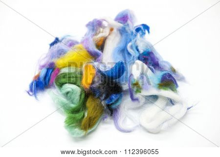 Multi-colored piece of Australian sheep wool Merino breed close-up on a white background