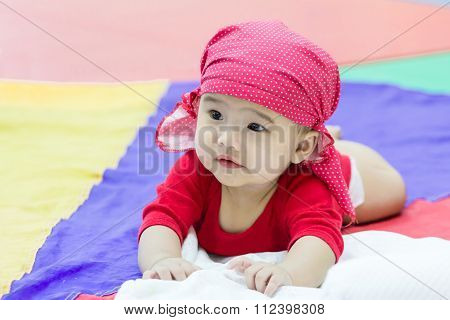 Asian Baby Prone On Colorful Fabric
