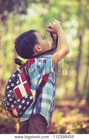Asian Boy With Digital Camera In Beautiful Outdoor. Retro Style.