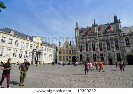 Bruges, Belgium - May 11, 2015: Tourist On Burg Square With City Hall In Bruges, Belgium