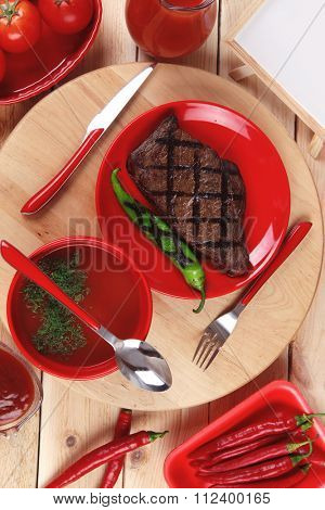 red theme lunch:fresh grilled bbq roast beef steak red plate green chili ketchup sauce paprika glass ground pepper american peppercorn modern cutlery served wood plate table empty nameplate menu board