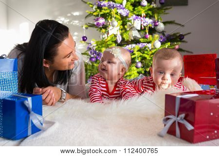 Mother with twins unpacking presents under the Christmas tree