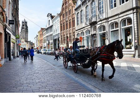 Bruges, Belgium - May 11, 2015: Tourists Visit Bruges In Traditional Horse Carriage Around The City