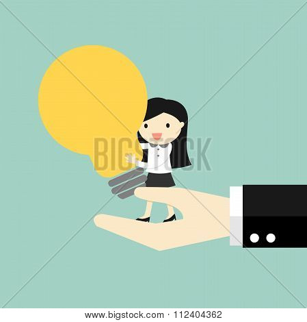 Business concept, Business woman standing on the big hand and holding big light bulb.