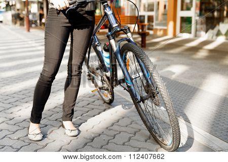 Legs of woman riding bike inn city
