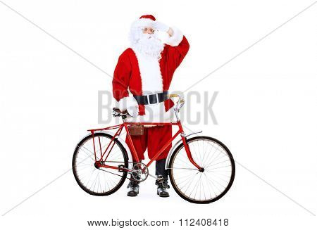 Active jolly Santa Claus rides his bicycle. Isolated over white background. Studio shot. Christmas concept.