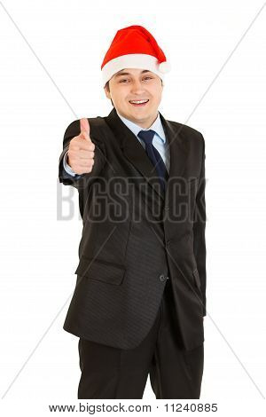 Happy young businessman in Christmas hat showing thumb up gesture isolated on white