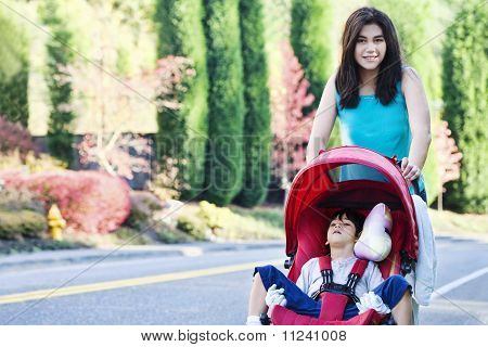 Teen pushing  disabled brother in stroller