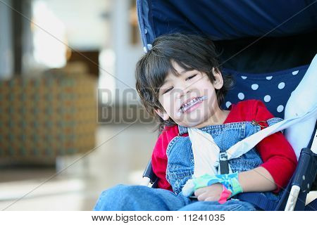 Cute Disabled Boy With Cerebral Palsy Smiling In Stroller