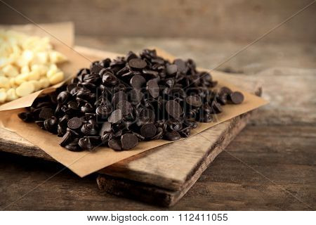 Chocolate morsels on board, on wooden background