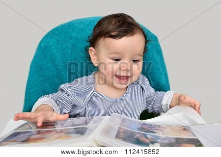 Smiling baby girl with photo album
