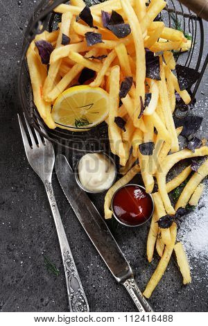French fries with sauce and tableware on table