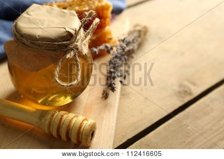 Glass jar with honey, honeycombs and nuts on wooden background
