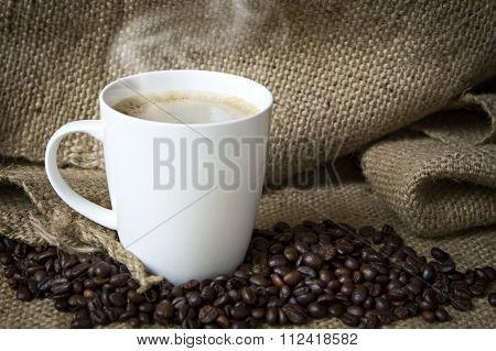Coffee Cup And Coffee Beans On Sack.