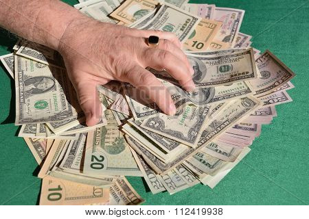 man's hand squeezes dollar bills