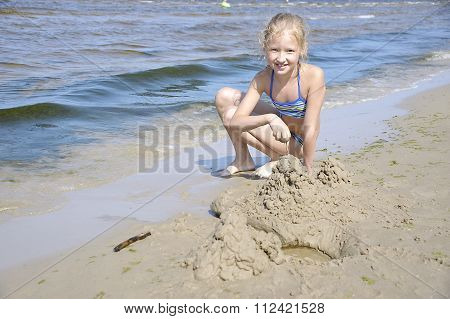 Jurmala. Girl Playing With Sand On The Beach.