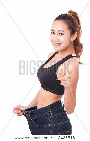 young slim woman wearing too big jeans with pointing finger on white background