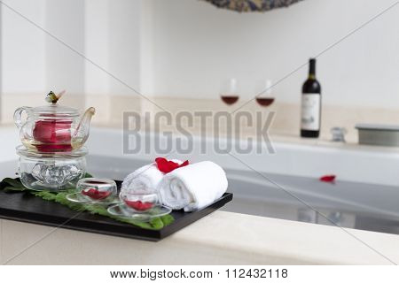 plate with teapot on beautiful white bathtub in which rose floating on water