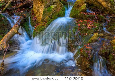 Small waterfall among green stones