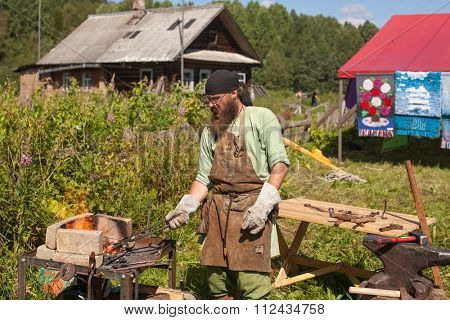SOGINITSY, RUSSIA - JULY 26, 2014: Unidentified Blacksmith participant during folk festival Ivan-Tea (lat. Chamaenerion) from ecovillage Grishino.