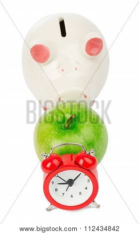 Apple with alarm clock and piggy bank