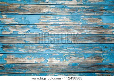 Old wooden plank wall with peeling blue paint