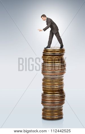Businessman bending from coins pile